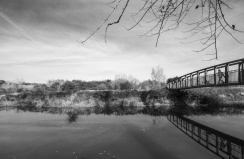 A contrasty image of a dog walker crossing the river Arun and the tranquil river meandering down towards Arundel