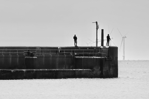 Detail of fishermen and turbines from across the harbour entrance