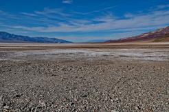 Down in Death Valley along Badlands Road, tourists walk the salt trails.